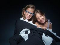 Två flickor sitter i en hajsovpåse