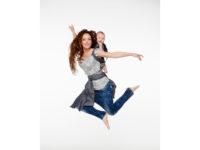 Kvinna som hoppar upp i luften. På ryggen sitter ett barn i en meitai deluxe.